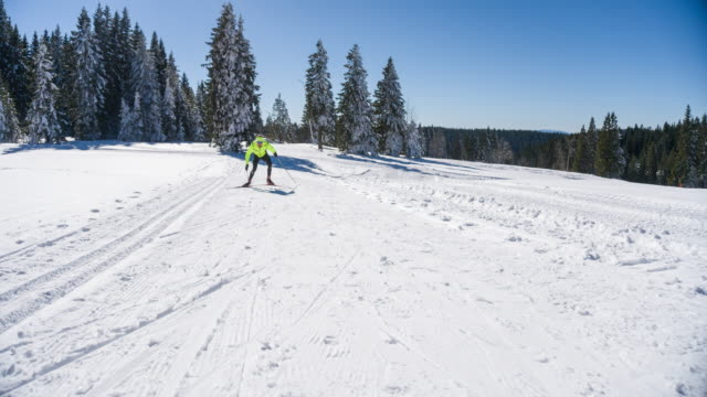 Professional cross country skier skate skiing uphill