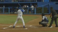 Professional Cuban baseball players playing baseball in a baseball stadium in Havana Cuba on January 27th 2015 Shots Wide shot of a player walking to...