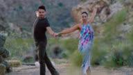SLO MO. Professional dancers twirl and strike elegant pose in scenic Nevada desert.