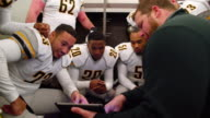 MS Professional football coach in locker room with team before game reviewing plays on digital tablet