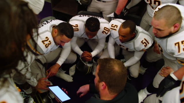 MS HA Professional football coach reviewing plays on digital tablet with team in locker room before game