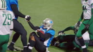 MS SLO MO. Professional football player helps teammate up and congratulates him after touchdown play.