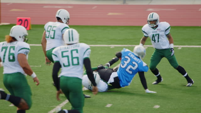 MS SLO MO. Professional football player is forcibly tackled by defensive cornerback.
