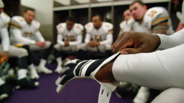 CU Professional football player putting on gloves while sitting with teammate in locker room before game