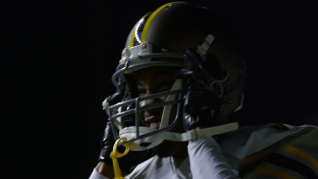 CU LA Professional football player putting on helmet before running out to field during night game