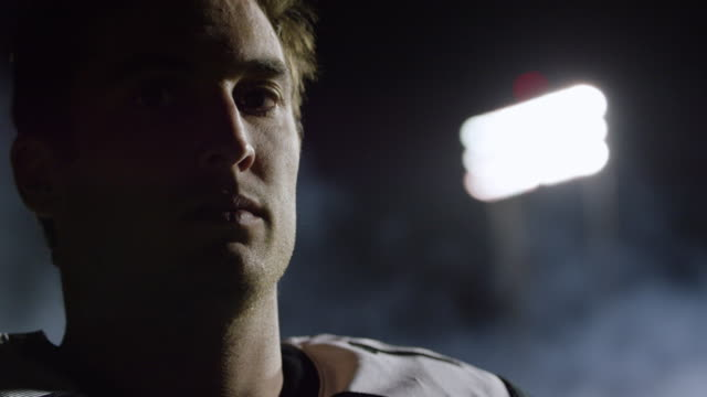 CU SLO MO. Professional football player turns and stares into camera under stadium lights.