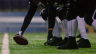 MS TU SLO MO Professional football players coming to line of scrimmage and snapping ball