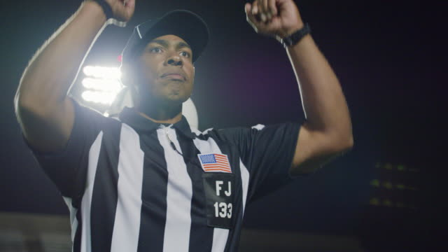 CU SLO MO. Professional football players cross frame as referee signals touchdown.