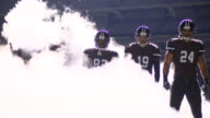 MS SLO MO Professional football players standing in fog on stadium field before game
