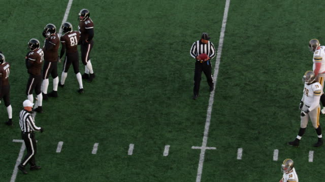 MS Professional football referee placing football on line of scrimmage
