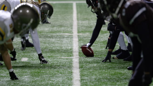 MS Professional football team coming to line of scrimmage and snapping ball during game
