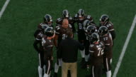 MS TS Professional football team discussing play with coach during timeout