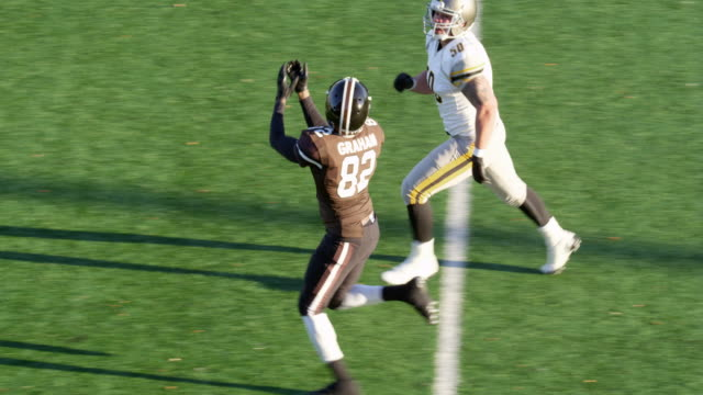 MS TS Professional football wide receiver running down sideline covered by defensive back and catching pass