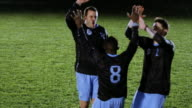 SLO MO TU professional soccer player being lifted on to shoulders of teammates in celebration on field