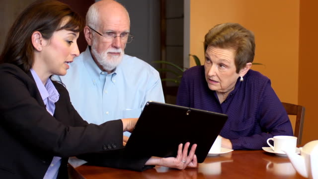 Professional Woman Interacts with Senior Couple using Digital Tablet