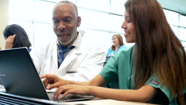 Professor encouraging nursing or medical student in college classroom