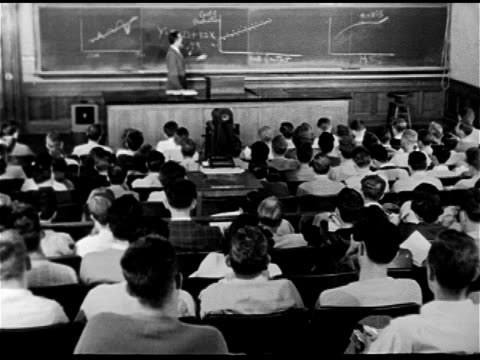 Professor standing at lecture room blackboard in front of formula w/ graph chart seated students FG WS Seated college students some older possibly GI...