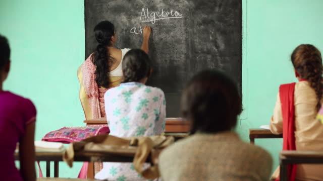Professor teaching university students in the classroom, Haryana, India