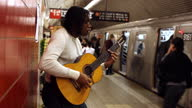 MED profile black man leans against red wall playing guitar in subway station   train enters   passengers board