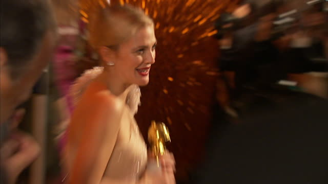 profile MCU Drew Barrymore posing with Golden Globe Award for paparazzi on the red carpet TD to award in her hands