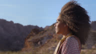 SLO MO. Profile of young woman closing her eyes as wind blows her hair in rocky desert landscape.