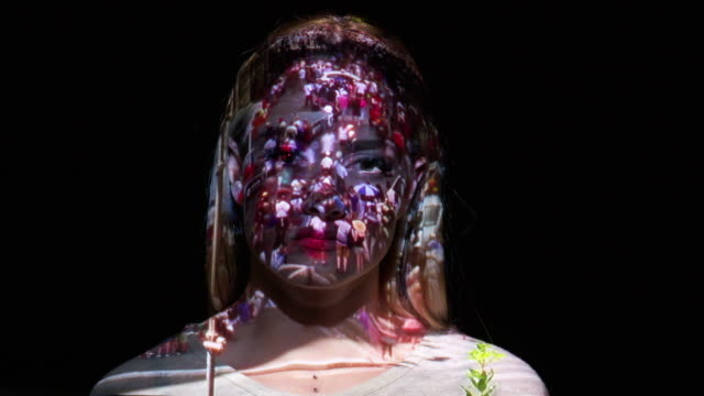 Projection of crowd timelapse on a woman's face