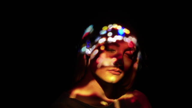 Projection of defocused traffic lights on a woman's face
