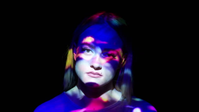 Projection of multicolored lights on a woman's face