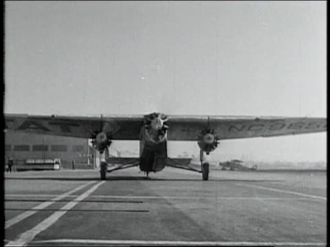 1928 MONTAGE Propeller airplane taxiing to hangar / Los Angeles, California, United States