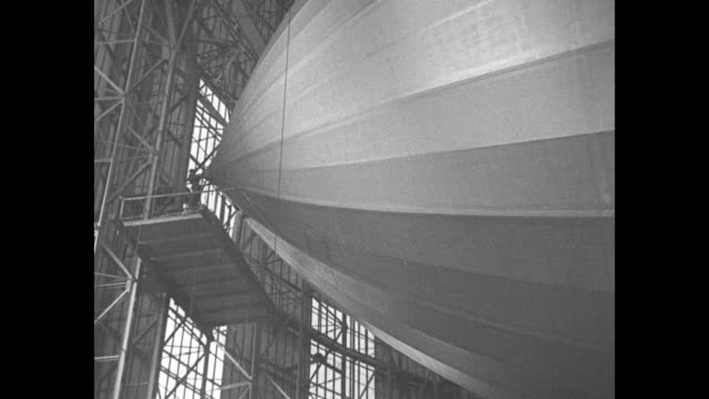 MS propeller of Hindenburg dirigible with inscription 'DLZ129' above on side of ship / worker stands on scaffolding at nose of airship as it sits in...