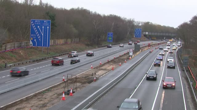 Proposals to increase speed limit through motorway roadworks R03041510 / Surrey M3 motorway EXT Various shots cars along motorway past roadworks and...