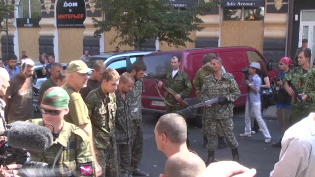 ProRussian separatists stand guard as dozens of Ukrainian prisoners dressed in ragged military uniforms and civilian clothes are marched past jeering...