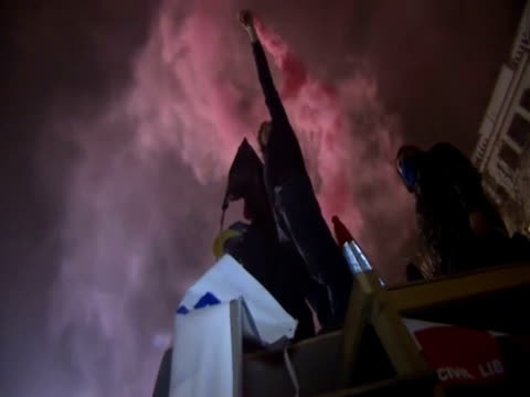 A protester at St Paul's Cathedral spreads red smoke during confrontations with bailifs