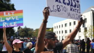 A protester holds a sign reading 'Blacks Whites Latinos Jews LGBTQs Muslims We Must Resist Hate' during the Bay Area Against Hate rally near the...