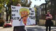 A protester holds a sign with an image depicting Donald Trump on a sign reading 'No Hate No Rasicm No no no Trump' near Alamo Square in San Francisco...