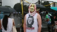 A protester wears a Guy Fawkes mask an American flag scarf and a tshirt depicting John Lennon as Che Guevara with the word 'Revolution' outside the...