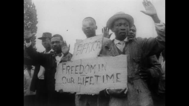 Protesters clash with police in Sharpeville / men hold a board that reads 'Freedom in our lifetime' / injured men sitting on the ground after police...