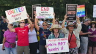 Protesters hold signs reading United Against Hate' End White Supremacy' and Altright AltWrong We're Not Havin' It' during the Bay Area Against Hate...
