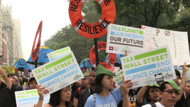 / protesters hold up signs as they march through the city streets including signs such as 'Tax Wall Street end climate change'
