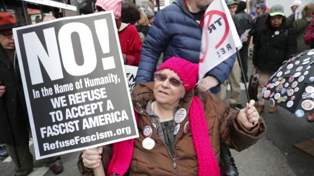 Protesters hold up signs for the Trump/Pence Must Go protest in NYC on November 4 2017 Photographer Jeenah Moon Shots shot of protester listening to...
