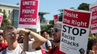 Protesters holding signs chant 'Immigrants in Nazis out' during the Bay Area Against Hate political protest rally near the Crescent in Berkeley...