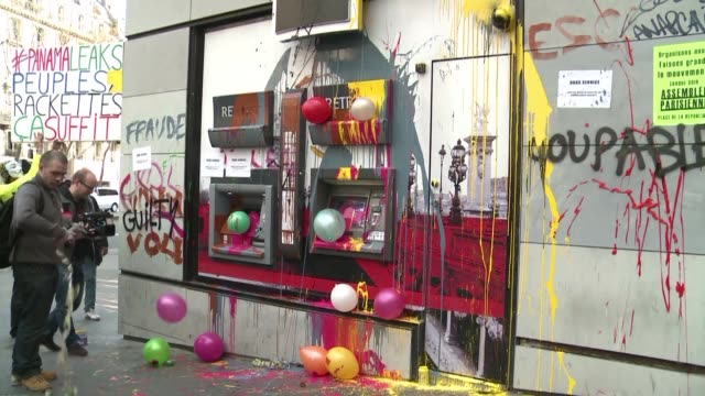 Protesters in Paris cover bank ATM machines in paint to show their discontent following the Panama Papers revelations