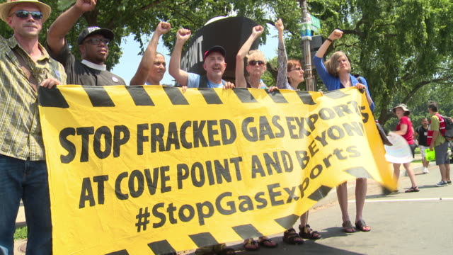 Protesters march chant and hold up signs against fracking and Cove Point