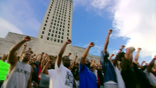 Protesters raising their arms in a display of solidarity for victims of police shootings outside the Louisiana State Capitol building