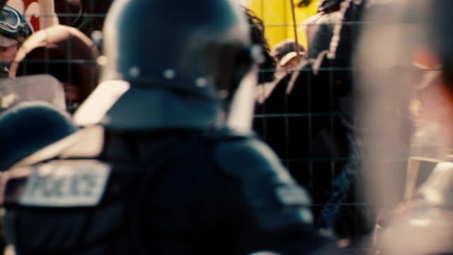 Protestors facing off against riot cops at a fence line.