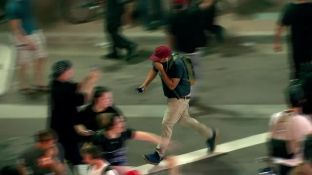 Protests outside Phoenix rally as President Donald Trump attacks the media Arizona Phoenix Crowd of protesters retreating as tear gas fired SOT Woman...