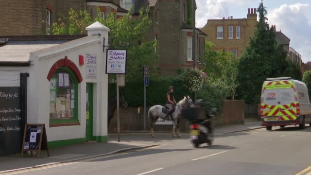 Protests over closure of Wimbledon riding school ENGLAND London Wimbledon EXT Riders along road on horseback Ridgway Stables sign with horse and...