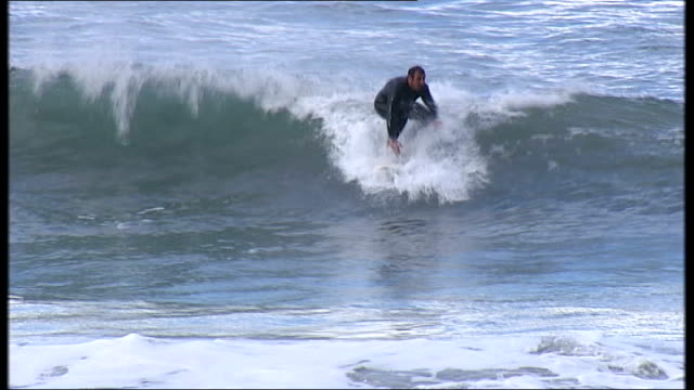 Protests over tough new abortion law Gijon EXT Various of surfer along on rough waves Reporter to camera