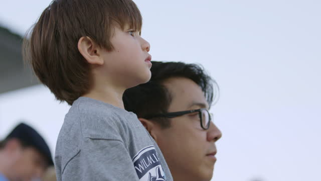 CU SLO MO. Proud sports fan lifts curious son up on stadium bleachers and points out action at big game.