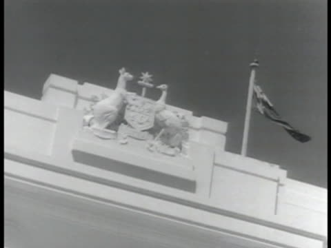 Provisional Parliament House w/ men walking on lawn Australian Coat of Arms near roof INT House of Representatives chamber WS Speaker seated in wig...